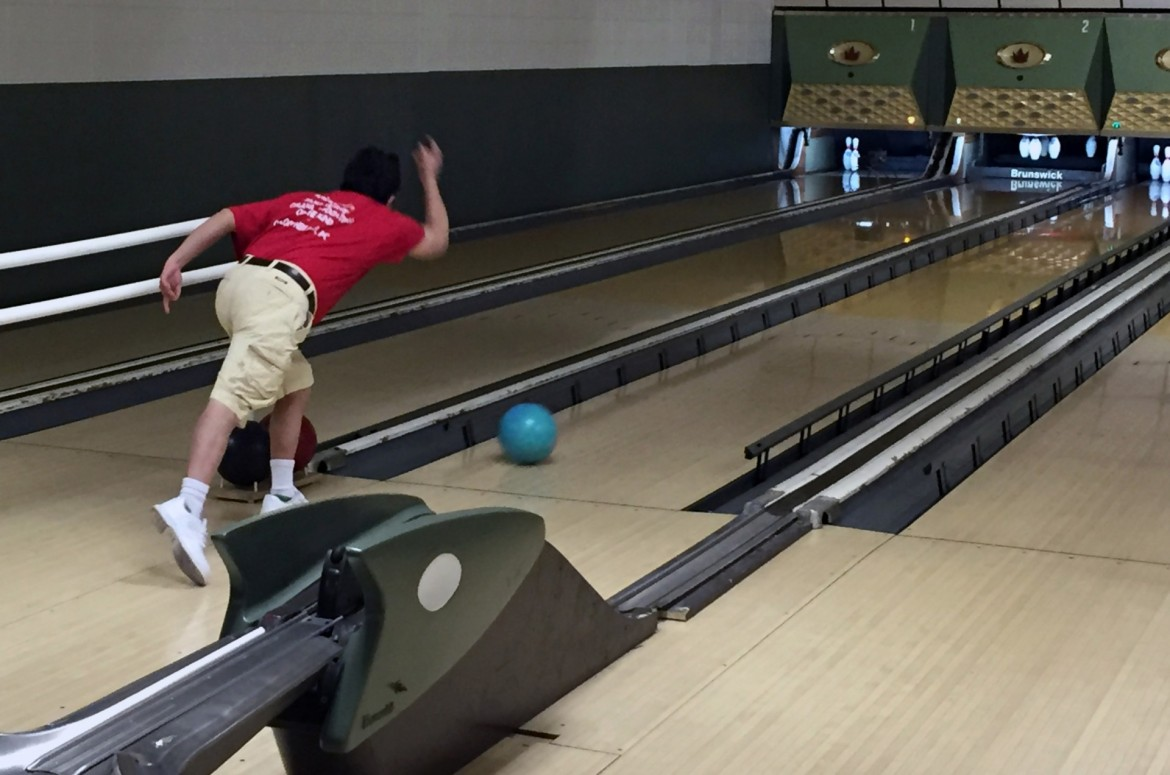 Image of a blind male rolling the bowling ball towards the pins at a bowling alley.