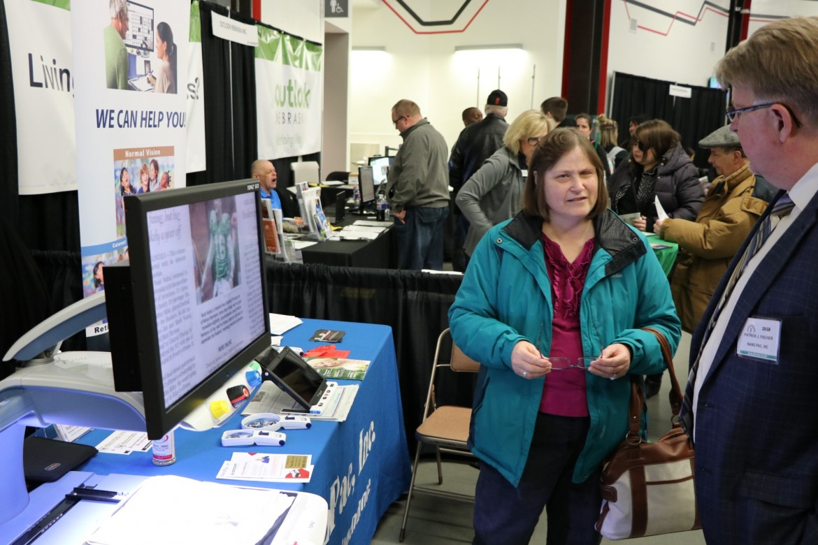 Image of visually impaired woman trying eSight eyewear at a booth during the resource fair.