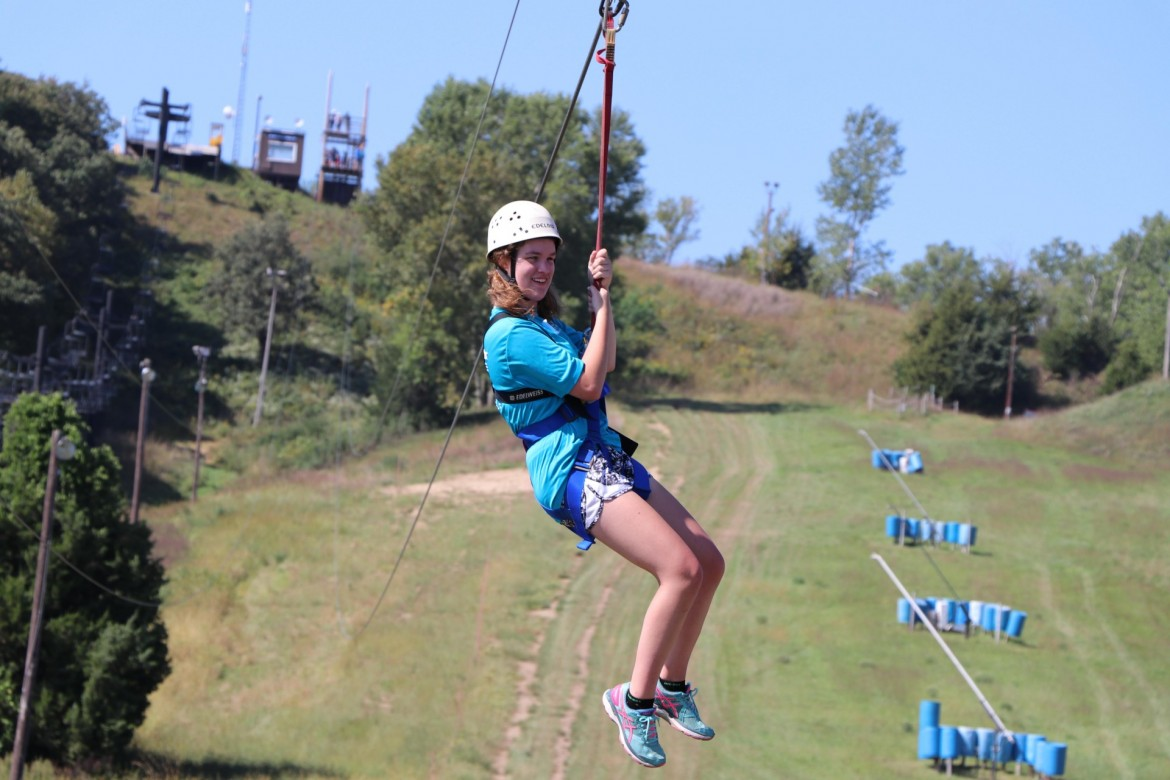 Image of youth recreation participant on zipline, smiling.