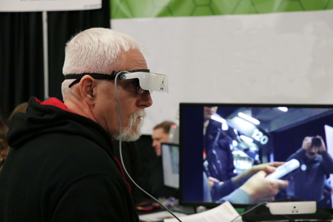 Image of man trying eSight digital eyewear at an event.