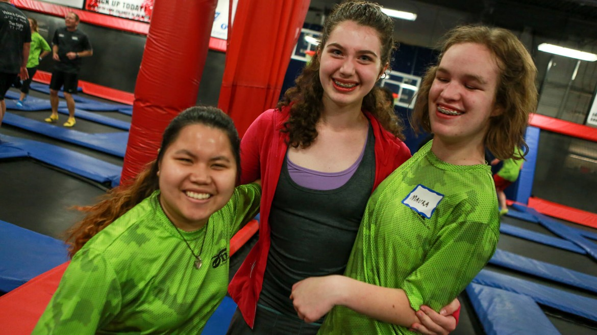 Three girls smiling at the trampoline park.