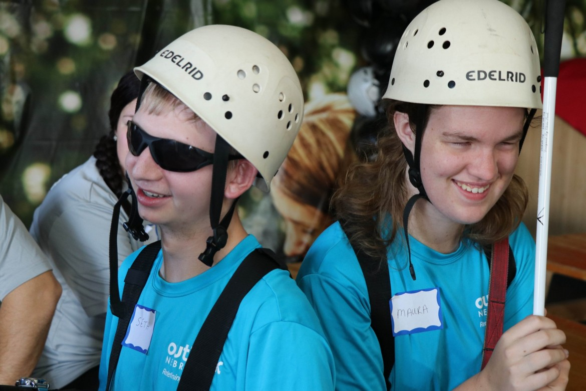 Image of teen recreation participants smiling while waiting to zipline.