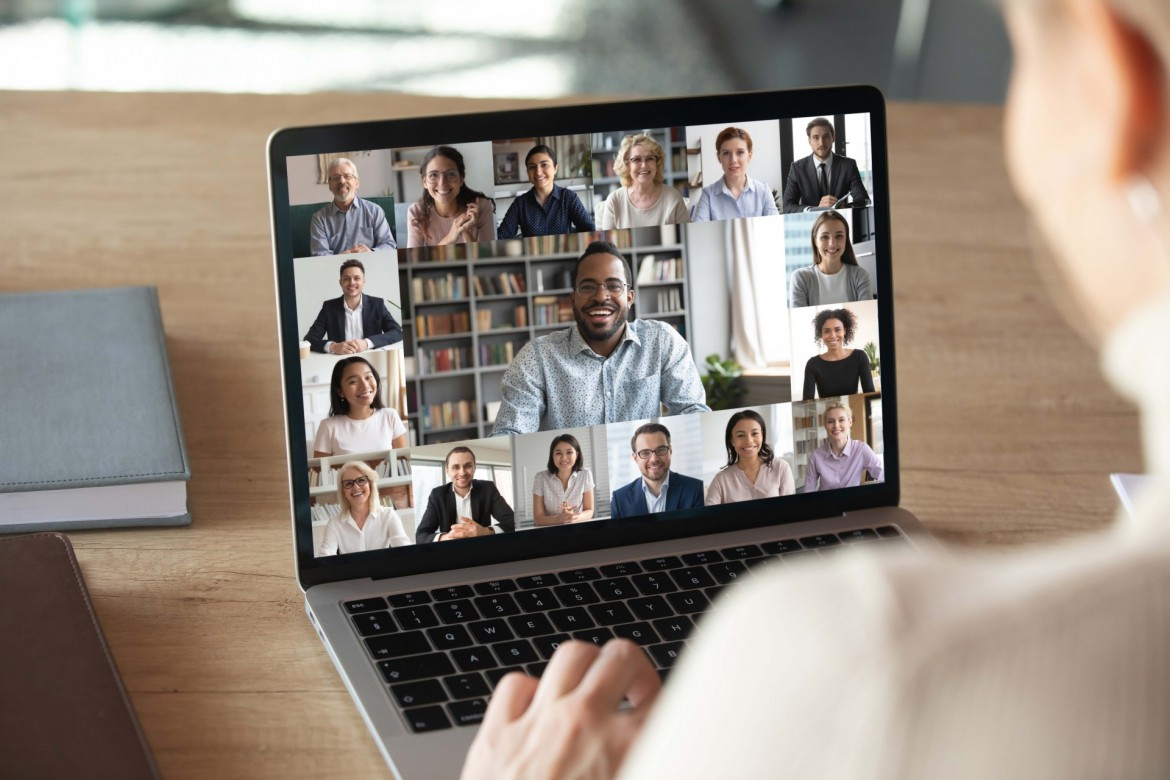 Image of person holding a laptop while looking at a group of people in a video chat.