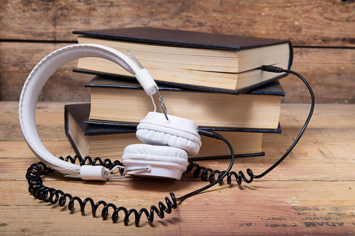 Image of a pair of headphones plugged into a stack of books