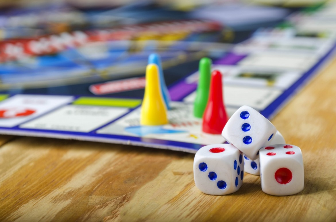 Image of board game with game pieces and dice towards the front of the image.