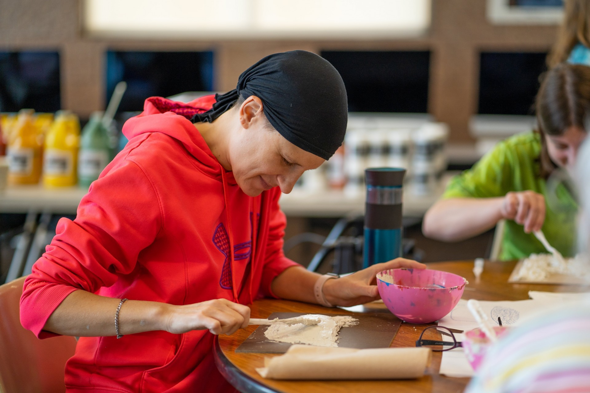 Image of woman working on an art project at a table in a Please Touch the Art class.