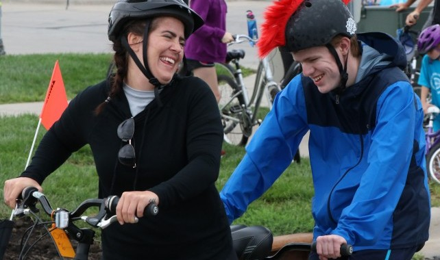 Image of sighted captain and visually impaired rider on tandem bike, smiling at each other.