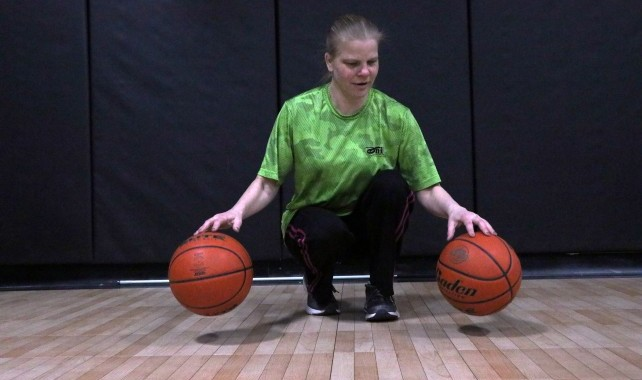 Image of visually impaired woman bouncing two basketballs at one time on basketball court.